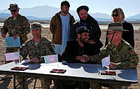 Colonel Wade Stothart, Commander Combined Team Uruzgan (right), signs over the airfield at Multi National Base - Tarin Kot to an Afghan government representative from the Ministry of Transport and Civil Aviation 12 December 2013.