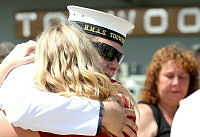 A crew member of HMAS Toowoomba says goodbye to his family, before the ship departs for the Middle East