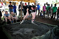 Private Jarrett Bugeja levels sand in a sandpit constructed by members of Combined Task Force 635 at the Private Jamie Clark Memorial Kindergarten.