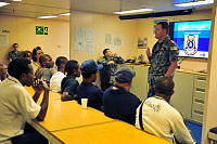 HMAS Choules Commanding Officer, Commander Ashley Papp, welcomes Manus Island Regional Processing Centre (MIRPC) staff aboard his ship. HMAS Choules is at Manus Island HMPNGS Tarangau, Lombrum Naval Base.