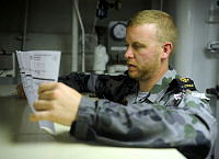 Leading Seaman Marine Technician Travis Spry prepares a postal vote while berthed at Aqaba, Jordon during the 2013 elections.