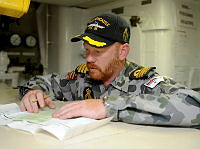 HMAS Newcastle's Commanding Officer Commander Paul O'Grady prepares to conduct a postal vote while berthed at Aqaba, Jordon during the 2013 Australian Government elections.