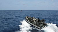 A Navy rigid hull inflatable boat (RHIB) from HMAS Wollongong is launched to conduct a fisheries boarding of a fishing vessel.