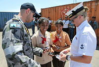 Able Seaman Giulio Carbanari and Leading Seaman Zoey Macqueen hand out koalas to the girl guides, who were a part of the welcoming party for HMAS Wollongong alongside Kupang, West Timor.