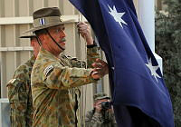 Warrant Officer Class One Geoffrey Stoakes, Regimental Sergeant Major of Rotary Wing Group - Eight, lowers the Australian flag signifying the end of mission for the contingent.