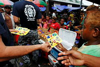 Ship's Company of HMAS Diamantina hand out explosive ordnance awareness disposal pamphlets to promote safety at Honiara Central Markets during Operation Render Safe in Solomon Islands.