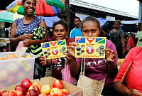 Agnas Mahete and Patricia Toro hold up explosive ordnance disposal awareness pamphlets at Honiara Central Markets as part of Operation Render Safe in Solomon Islands.