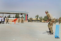 Major Gavin Rudrum, advisor at 205 CAT, Kandahar, winding up to hit a 'six' during the inaugural 'Afghan Ashes' cricket match at Camp Hero.
