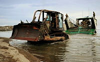 An Australian Army bulldozer disembarks a landing craft onto a beach in Ormoc, Philippines, during Operation PHILIPPINES ASSIST.