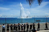 Members of Combined Joint Task Force 663, the Australian Federal Police and the Royal Solomon Islands watch a controlled detonation conducted by Operational Dive Team Royal New Zealand Defence Force off the coast of Guadalcanal Beach Resort during Operation RENDER SAFE 13.