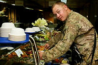 Corporal Steven Miller from Taskforce Mustang helps himself to a Thanksgiving dinner and the final meal prepared at Multi National Base Tarin Kot on November 28.