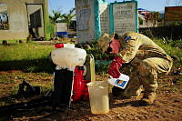 Sergeant Emma Franklin from 2nd General Health Battalion prepares mosquito control chemicals which will be applied to the exterior of the buildings at Liloan National High School in Ormoc City.