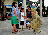 Students from Ipil Central School in Ormoc City give Australian Army Officer, Captain Shad March from Headquarters 1 Division in Brisbane, thank you letters for the clean-up of their school by Australian Defence Force personnel during Operation PHILIPPINES ASSIST.