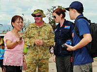 School Principle of Cogon Central School in Ormoc, Miss Editha Laurente, chats with the Australian Government Civil-Military Cooperation team at Ormoc during a visit following a clean-up by Australian Defence Force personnel.
