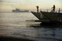 An Army landing craft from 10th Force Support Battalion arrives at San Antonio beach near Ormoc City to load machinery and trucks onto HMAS Tobruk (background).