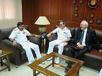 Commander Combined Task Force 150, Commodore Daryl Bates demonstrates use of the 'emu caller', a gift he is presenting to Commander Pakistan Fleet, Vice Admiral Khan Hasham Bin Saddique