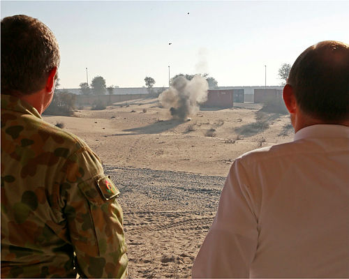 Royal Australian Air Force Sergeant Iain McPhail (left) demonstrates the destructive force of a small amount of military grade explosives to the Prime Minister of Australia, the Honourable Tony Abbott, MP, at the Explosives Ordnance range in the Middle East Region.