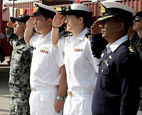 Officers salute as the National Anthems are played for Australia and Bangladesh by the Bangladesh Navy Band at the official welcoming of HMAS Childers to Bangladesh.