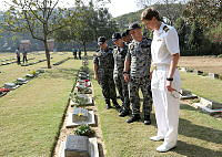 Crew members of HMAS Childers gather around a Royal Australian Air Force Force plaque at the Chittagong War Cemetery, during the boats port visit to Bangladesh.