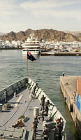 PSailors on the forecastle of HMAS Darwin, secure the berthing lines, as the ship comes alongside the Port Sultan Qaboos.