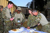 Lance Corporal Raymond Doyle (far right), cuts and serves cake to other Australian personnel during the Australian Army and Royal Australian Navy birthday celebrations at Camp BAKER, Kandahar.