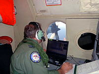 A Royal Australian Air Force crew member of an AP-3C Orion maritime patrol aircraft keeps track of the aircrafts progress to the west of Peninsula Malaysia during the search for Malaysian Airlines Flight MH370. In the background an aircraft propeller stands idle, testament to the fuel-saving measures taken by the crew to maximise their time spent searching.