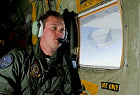 Royal Australian Air Force (RAAF) loadmaster Sergeant Adam Roberts scans the ocean while onboard a C-130J Hercules as it flies over the southern search area in the southern Indian Ocean as part of the Australian Defence Force's assistance to the search for Malaysia Airlines flight MH370.