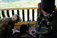 Philippines Army soldier, Private First Class A (centre) receives marksmanship training from Australian soldier Private B (left) a member of the 2nd Commando Regiment, while Private First Class B provides spotting assistance at Fort Magsaysay, Philippines, during Exercise Balikatan.