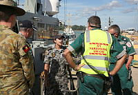 Australian Defence Force personnel from HMAS Wollongong assist Northern Territory paramedics to move one of the injured Australian civilian sailors transferred to Darwin by HMAS Wollongong into the waiting ambulance.