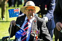 Australian D-Day veteran Bill Evans waves the Australian National Flag during a service commemorating the 70th anniversary of the D-Day landings in Bayeux War Cemetery, France.