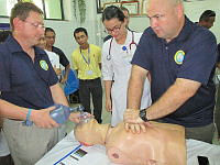 Royal Australian Navy Lieutenant Craig Blackburn (left) and Flight Lieutenant Ben James (right) from the Royal Australian Air Force demonstrate CPR procedures for doctors and nurses at Da Nang General Hospital in Vietnam.