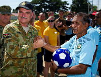 Royal Australian Air Force officer Wing Commander Daryll Topp (left) gifts a soccer ball to Dominic De Jesus after a friendly game of soccer against local Timor- Leste community leaders during Pacific Partnership 2014 in Dili, East Timor.