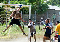 Australian soldier Sapper Patrick Gorrie from 21 Construction Squadron, 6 Engineer Support Regiment, leaps high to head butt a ball clear from the goal during a friendly soccer match against local Timor-Leste community leaders during Exercise Pacific Partnership 2014, in Dili, East Timor.