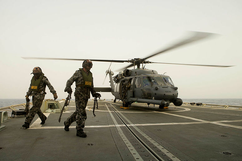 Able Seaman Aviation Technician Aircraft (ABATA) Wayde Silcock (right) and ABATA Andrew Woolfe remove chains used to secure the United States Air Force Pave Hawk helicopter to HMAS Darwin's flight deck.