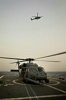 Two United States Air Force Pave Hawk helicopters take it in turns of landing and taking off using the flight deck of HMAS Darwin.