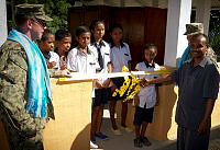 Director of Comoro Intermediate School Filomeno Salsimha (right) cuts the ribbon to the newly-built kitchen at the Comoro Intermediate School in Dili, East Timor, during Exercise Pacific Partnership 2014.