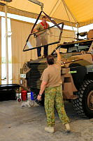 Geoff Molles, part of the Protected Mobility Vehicle upgrade team, guides the old front window with Team Leader Major Craig Byrne assisting, as part of the upgrades at Al Minhad Air Base.