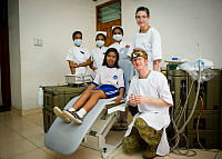Royal Australian Air Force Leading Aircraftwoman Teagan Walker (back right), Royal Australian Air Force officer Flight Lieutenant Ben Cosson, Amelia dos Santos (in chair) and Timorese trainee nurses pose for a photo at Comoro Medical Centre in Dili, East Timor, during Exercise Pacific Partnership 2014.