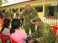 Australian Defence Force nurses (Flight Lieutenant Ben James of the Royal Australian Air Force is at centre) examine a local lady during a MEDCAP conducted at the Takeo Teacher Training Centre.