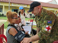 Flight Lieutnant Ben James, of Ipswich QLD, conducts a health check on a Khmer lady during a free medical clinic conducted under the auspices of Pacific Partnership 14 at The Hun Sen Primary School in Sihanoukville.