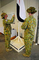 Regimental Sergeant Major Warrant Officer Class 1 Vikke Patterson (left), lowers the Force Communications Unit-10 flag for the last time prior to presenting it to the Commander Joint Task Force 633, Major General Craig Orme.