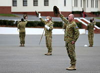 Australian Army Band Musical Director, Major Dan Hiscock, and the Australian Army Band raise their slouch hats while they rehearse the song 'Brown Slouch Hat' on the Royal Military College – Duntroon parade ground prior to departing for the 2014 Basel International Tattoo, Switzerland, from July 14-26.