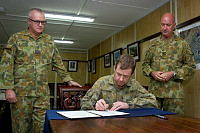 Wing Commander David Howard (centre) transfers Command of the Air Component to Wing Commander Steve Laredo (left) while watched by Commander Joint Task Force 633 Major General Craig Orme (right).