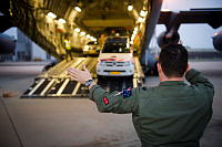 Royal Australian Air Force Sergeant Peter Clarke helps guide a Netherlands Defence Force vehicle onto a C-17A Globemaster at Eindhoven Airfield during the Australian Defence Force contribution to Operation Bring Them Home.