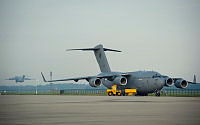 A Royal Australian Air Force C-17A Globemaster waits to be loaded with cargo while another takes off toward Ukraine, during Operation Bring Them Home.