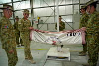 Regimental Sergeant Major, Force Support Unit-9 (FSU-9), Warrant Officer Class One Wayne McMillan and Company Sergeant Major, Force Support Element-1, Warrant Officer Class Two Gregg Orlicki fold the FSU-9 flag for the last time during the Transfer of Authority and medals parade at Al Minhad Air Base.