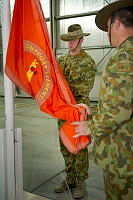 Officer Commanding Major Luke Condon raises the Force Support Element-1 flag during the Transfer of Authority and medals parade at Al Minhad Air Base.