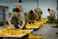 Private Toby Rogalski, a Parachute Rigger with 176 Air Dispatch Squadron, prepares a skid board for an airdrop bundle of humanitarian aid.