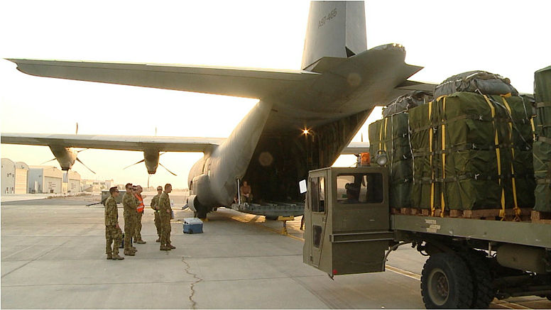 A Trailer Aircraft Loading Unloading (TALU) edges forward to the tail ramp of a Royal Australian Air Force (RAAF) C-130J Hercules transport aircraft. The TALU is loaded with airdrop bundles of humanitarian aid that will soon be dropped by the Hercules to isolated Iraqi civilians on Mount Sinjar in northern Iraq.