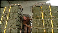 A Royal Australian Air Force (RAAF) loadmaster checks airdrop bundles of humanitarian aid prior to being loaded into a RAAF C-130J Hercules transport aircraft for delivery to isolated Iraqi civilians on Mount Sinjar in northern Iraq.